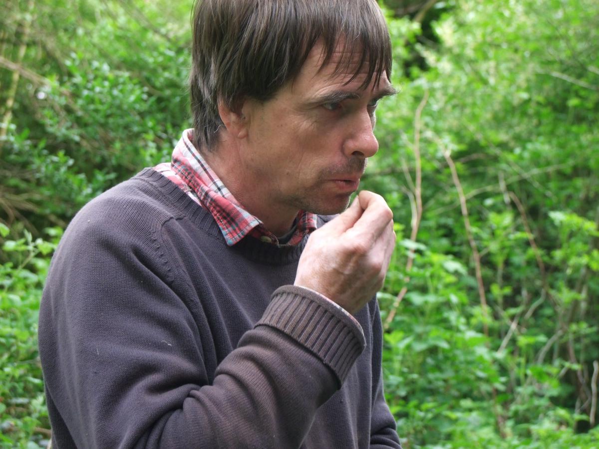 Martin Crawford goûte une fleur de sa forêt jardin - crédit Diana Semaska